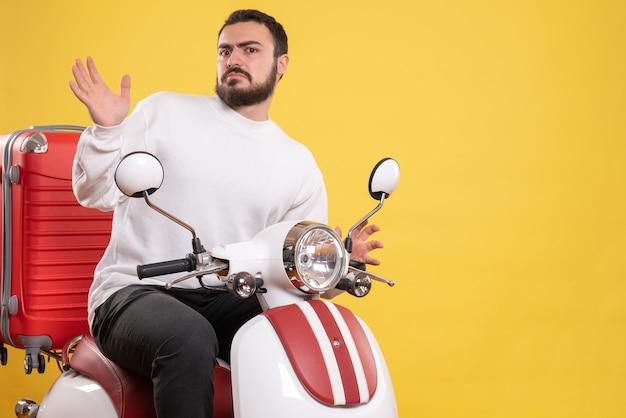 Bovenaanzicht van verwarde jonge kerel zittend op motorfiets met koffer erop op geïsoleerde gele achtergrond