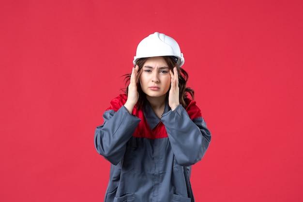 Bovenaanzicht van verwarde vrouwelijke bouwer in uniform met helm op geïsoleerde rode achtergrond