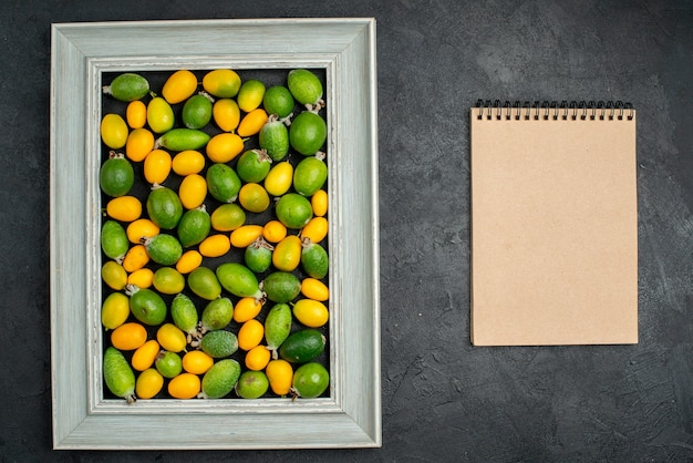 Bovenaanzicht van verzameling citrusvruchten in fotolijst en spiraalvormig notitieboekje op donkere tafel