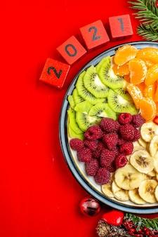 Bovenaanzicht van verzameling van vers fruit op diner plaat decoratie accessoires fir takken en cijfers op een rood servet