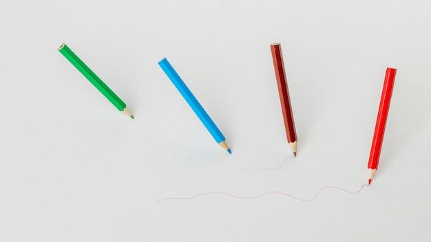 Bovenaanzicht van vier kleurpotloden tekenen op een witte achtergrond. schrijfwaren en schoolbenodigdheden.
