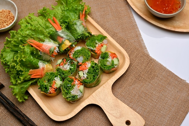 Bovenaanzicht van vietnamese loempia's op houten dienblad serveren met dipsaus