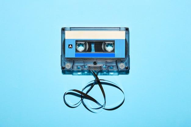 Bovenaanzicht van vintage ouderwetse plastic compacte audiocassette met verwarde tape op blauw