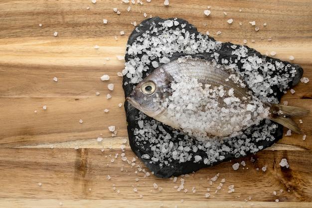 Bovenaanzicht van vis op leisteen met zout