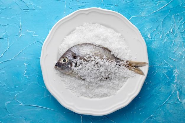 Bovenaanzicht van vis op plaat met zout