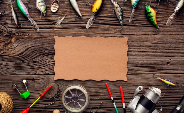 Bovenaanzicht van visgerei frame met veelkleurige aas en stuk papier