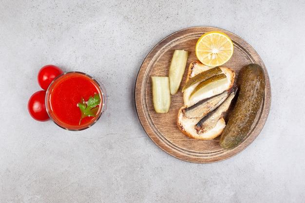 Bovenaanzicht van vissandwich met augurk en saus op grijze ondergrond.