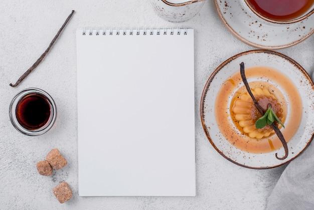 Bovenaanzicht van vla op plaat met munt en notebook