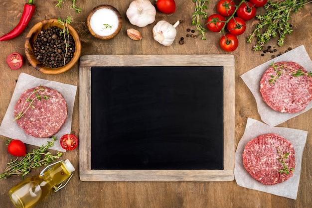 Bovenaanzicht van vlees met kruiden en schoolbord