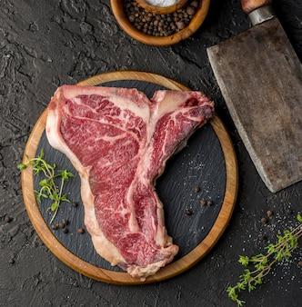 Bovenaanzicht van vlees op leisteen met kruiden en specerijen