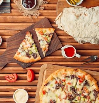 Bovenaanzicht van vlees pizza plakjes op hout snijplank