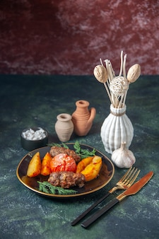 Bovenaanzicht van vleeskoteletten gebakken met aardappelen en tomaat geserveerd met groene bestekset zout knoflook op mix kleuren achtergrond