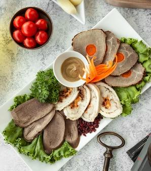Bovenaanzicht van vleespastei schotel geserveerd met wortel en saus