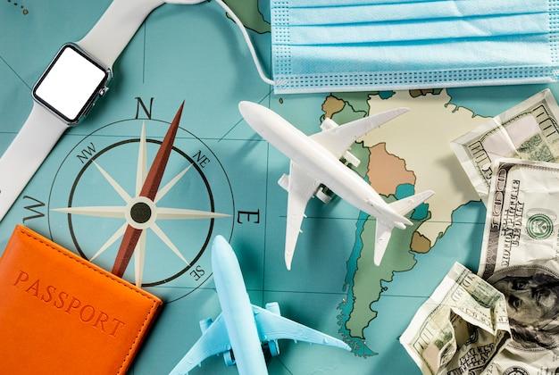 Bovenaanzicht van vliegtuigbeeldjes met smartwatch en medisch masker