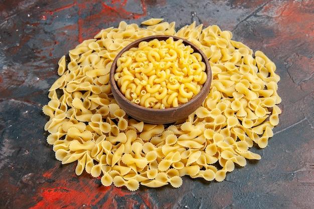 Bovenaanzicht van vlinder ongekookte pasta's in een bruine kom op gemengde kleur achtergrond