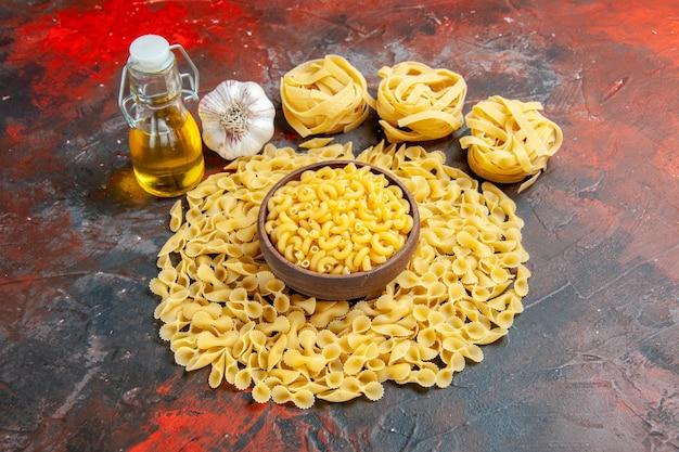 Bovenaanzicht van vlinder ongekookte pasta's in een bruine kom spaggeti knoflook en olie fles op gemengde kleur achtergrond