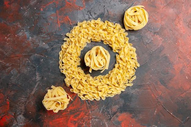 Bovenaanzicht van vlinderpasta en spaghetti op gemengde kleurentafel