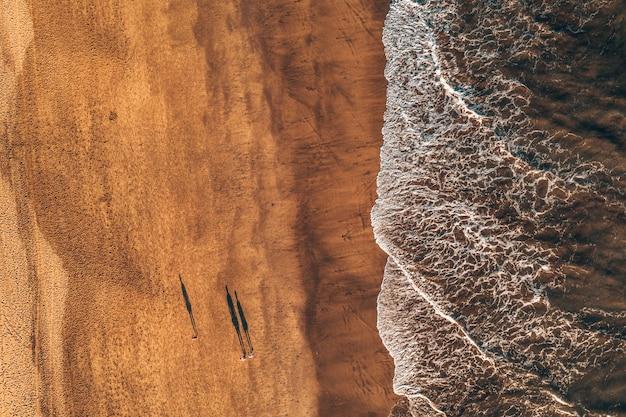 Bovenaanzicht van vloedgolven die op het zand komen