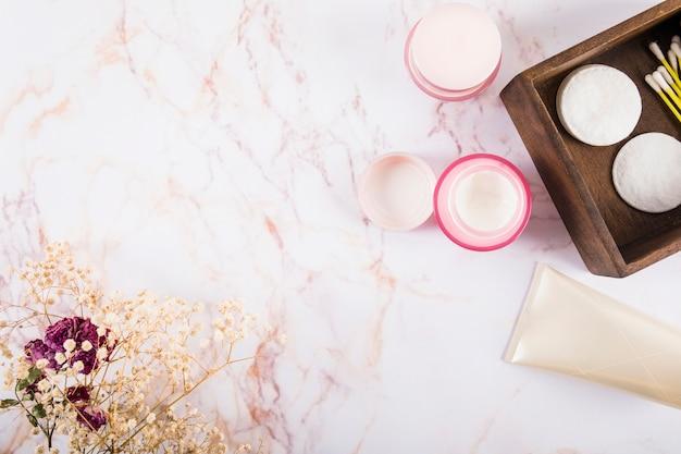 Bovenaanzicht van vochtinbrengende crème en bloemen op marmer