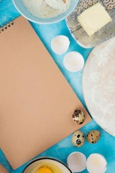 Bovenaanzicht van voedsel als ei en boter met eierschaal op blauwe achtergrond met kopie ruimte