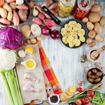 Bovenaanzicht van voedsel en groenten als zure tomaat kippenpoot gebakken aardappel kool bloemkool selderij en anderen op houten achtergrond met kopie ruimte