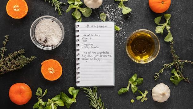 Bovenaanzicht van voedselingrediënten met kruiden en notitieboekje