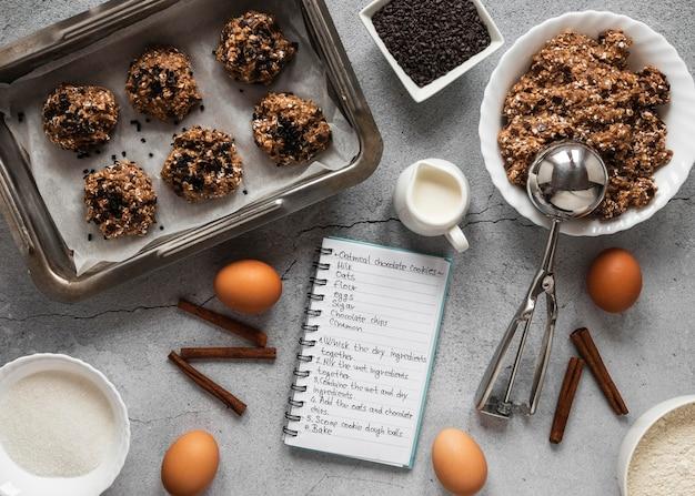 Bovenaanzicht van voedselingrediënten met notitieboekje en dessertmix