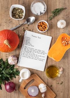 Bovenaanzicht van voedselingrediënten met notitieboekje en pompoen