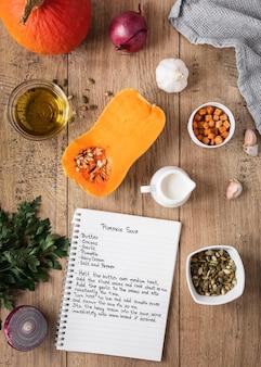 Bovenaanzicht van voedselingrediënten met pompoen en notitieboekje