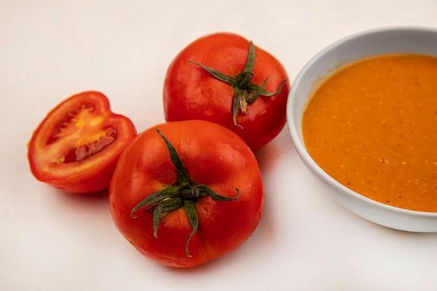 Bovenaanzicht van voedzame linzensoep op een kom met tomaten geïsoleerd op een witte muur