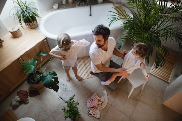 Bovenaanzicht van volwassen vader met twee kleine kinderen binnenshuis die zich klaarmaken voor een bad