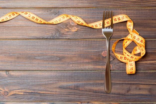 Bovenaanzicht van vork en gekrulde meetlint op houten achtergrond. dieet concept met kopie ruimte