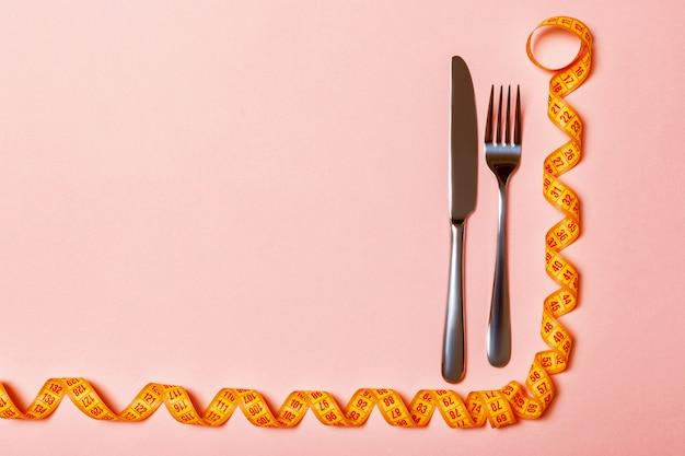 Bovenaanzicht van vork en mes en gekrulde meetlint. dieet concept met kopie ruimte