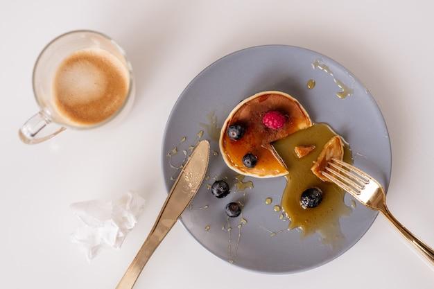 Bovenaanzicht van vork en mes op plaat met smakelijke zelfgemaakte pannenkoek met honing en verse bramen met mok koffie in de buurt