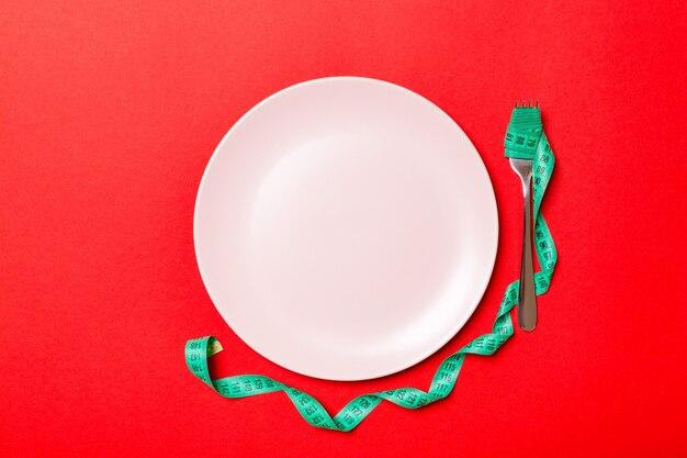 Bovenaanzicht van vork met meetlint in de buurt van ronde plaat op rood
