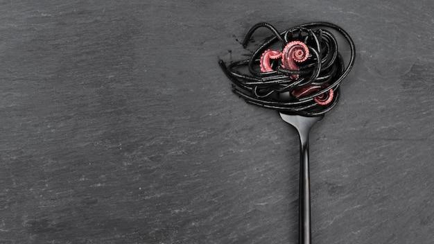 Bovenaanzicht van vork met zwarte spaghetti en inktvis