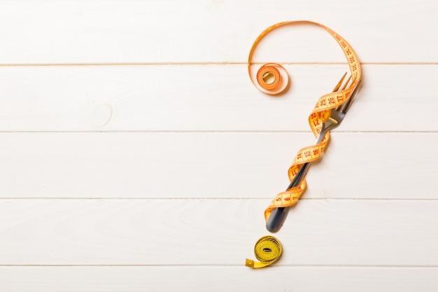Bovenaanzicht van vraagteken gemaakt van vork en meetlint op houten achtergrond. dieet concept met kopie ruimte