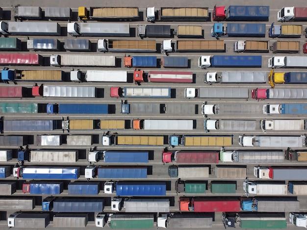 Bovenaanzicht van vrachtwagens die in de rij staan voor het lossen in de haven.