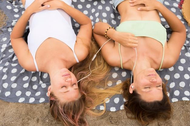Bovenaanzicht van vriendinnen ontspannen op het strand