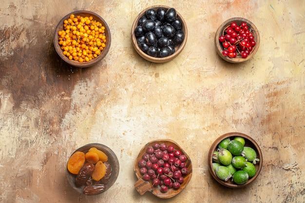 Bovenaanzicht van vrije plaats tussen vers verschillende soorten fruit in kleine bruine potten