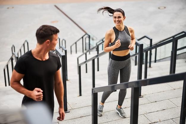 Bovenaanzicht van vrolijke atletische man en vrouw in sportkleding die naar boven loopt in het stadscentrum