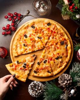 Bovenaanzicht van vrouw die een plakje kip pizza