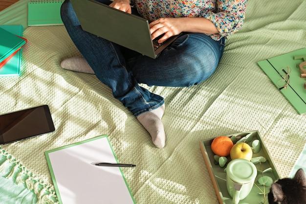 Bovenaanzicht van vrouw die werkt in de informele omgeving met haar laptop, kladblok, kopje thee. werk op afstand, thuiskantoor, freelancer, zelfisolatieconcept
