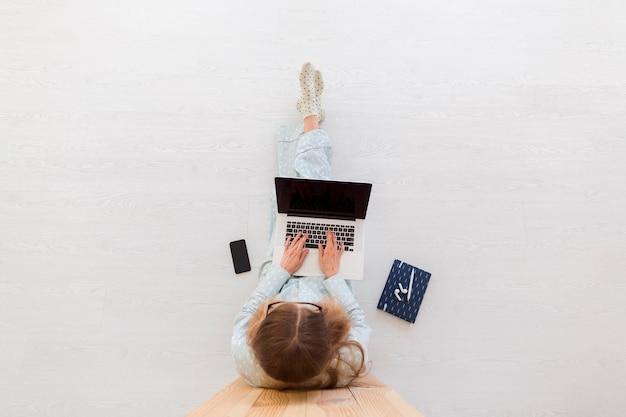 Bovenaanzicht van vrouw die werkt vanuit huis op laptop in pyjama