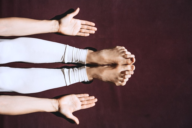 Bovenaanzicht van vrouw die yoga beoefent close-up van vrouwelijke voeten en handpalmen op yogamat met kopieerruimte