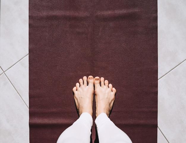 Bovenaanzicht van vrouw die yoga beoefent close-up van vrouwelijke voeten op yogamat met kopieerruimte