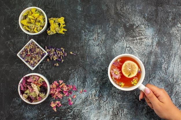 Bovenaanzicht van vrouw hand met een kopje kruidenthee en drie kommen droge bloemen op grijze grond