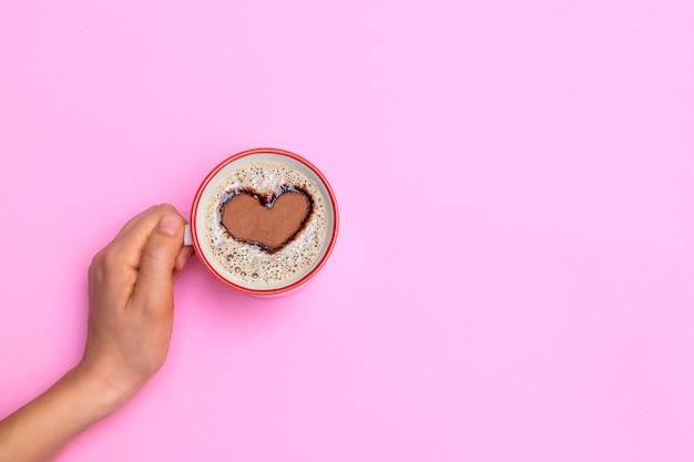 Bovenaanzicht van vrouw hand met een mok met cappuccino of latte met hart getrokken