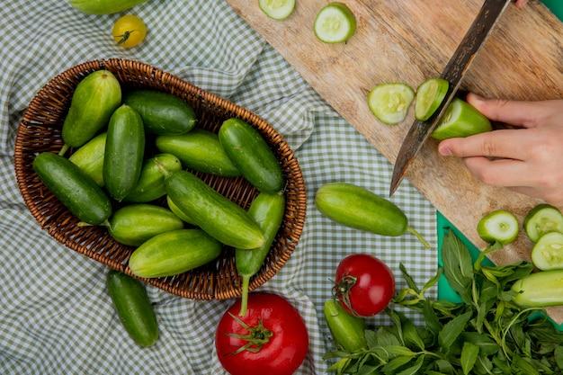 Bovenaanzicht van vrouw hand snijden komkommer met mes op snijplank met andere in mand tomaten en munt op geruite doek oppervlak