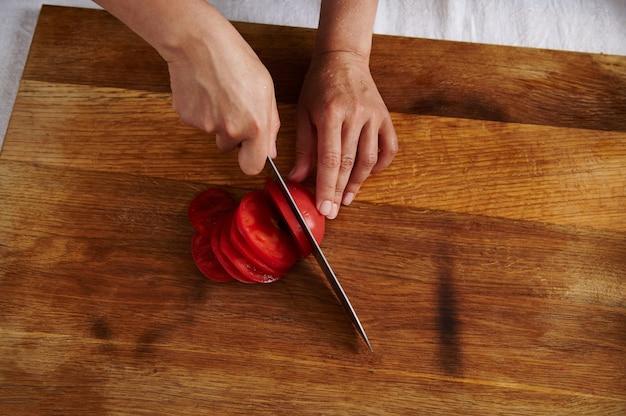 Bovenaanzicht van vrouw hand snijden tomaat op een houten bord